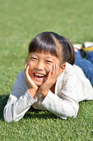 野原で頬杖をつく女の子の写真素材 [FYI00623537]