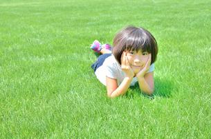 野原で頬杖をつく女の子の写真素材 [FYI00623548]