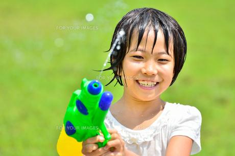 芝生広場で水鉄砲遊びを楽しむ女の子の写真素材 [FYI00623678]