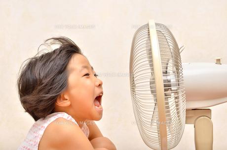扇風機で涼む女の子の写真素材 [FYI00623682]