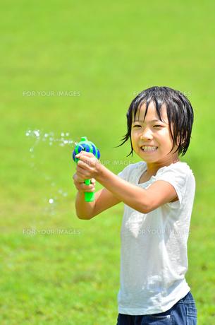 芝生広場で水鉄砲遊びを楽しむ女の子の写真素材 [FYI00623686]