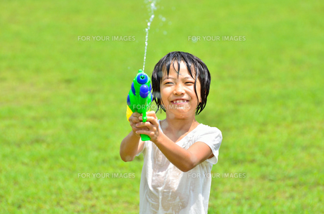 芝生広場で水鉄砲遊びを楽しむ女の子の写真素材 [FYI00623687]
