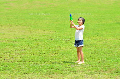 芝生広場で水鉄砲遊びを楽しむ女の子の写真素材 [FYI00623688]