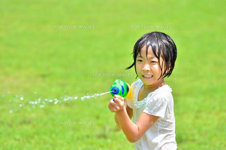 芝生広場で水鉄砲遊びを楽しむ女の子の写真素材 [FYI00623689]