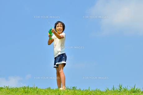 青空で水鉄砲遊びを楽しむ女の子の写真素材 [FYI00623690]