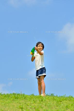 青空で水鉄砲遊びを楽しむ女の子の写真素材 [FYI00623691]