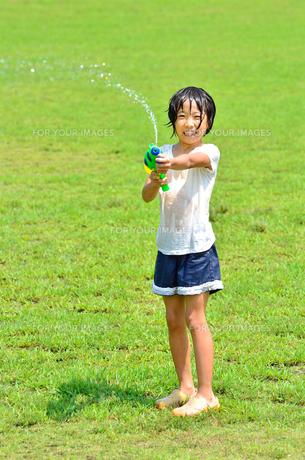 芝生広場で水鉄砲遊びを楽しむ女の子の写真素材 [FYI00623692]