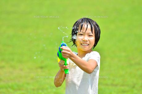 芝生広場で水鉄砲遊びを楽しむ女の子の写真素材 [FYI00623693]