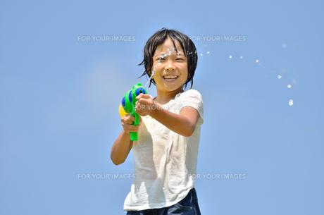 青空で水鉄砲遊びを楽しむ女の子の写真素材 [FYI00623694]