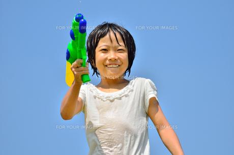 青空で水鉄砲遊びを楽しむ女の子の写真素材 [FYI00623696]