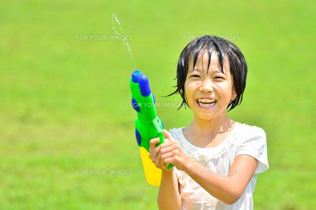 芝生広場で水鉄砲遊びを楽しむ女の子の写真素材 [FYI00623697]
