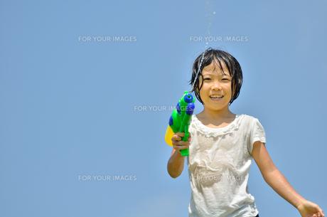青空で水鉄砲遊びを楽しむ女の子の写真素材 [FYI00623698]
