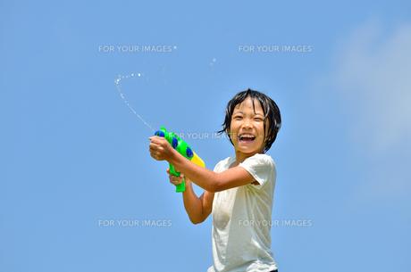 青空で水鉄砲遊びを楽しむ女の子の写真素材 [FYI00623699]