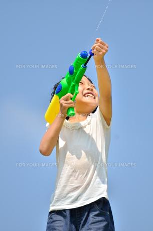 青空で水鉄砲遊びを楽しむ女の子の写真素材 [FYI00623700]