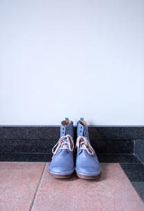 玄関に置かれたヴィンテージの青いブーツの写真素材 [FYI00625125]