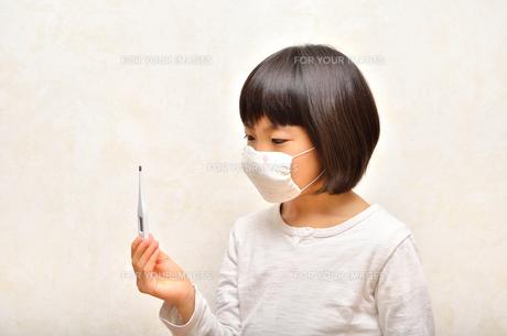 体温計を持つマスク姿の女の子(風邪)の写真素材 [FYI00625772]