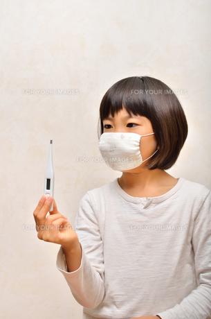 体温計を持つマスク姿の女の子(風邪)の写真素材 [FYI00625779]