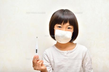 体温計を持つマスク姿の女の子(風邪)の写真素材 [FYI00625780]