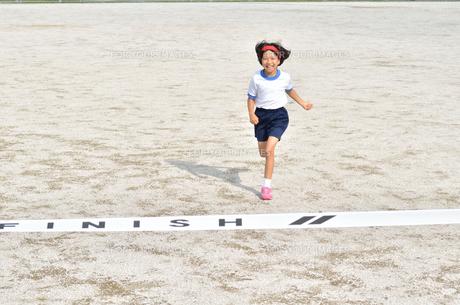 ゴールテープを切る小学生の女の子(グラウンド)の写真素材 [FYI00626798]