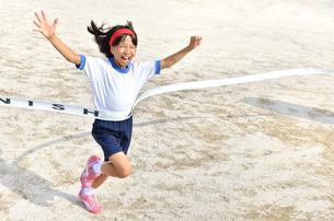 ゴールテープを切る小学生の女の子(グラウンド)の写真素材 [FYI00626799]