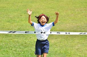 ゴールテープを切る小学生の女の子(芝生)の写真素材 [FYI00626801]