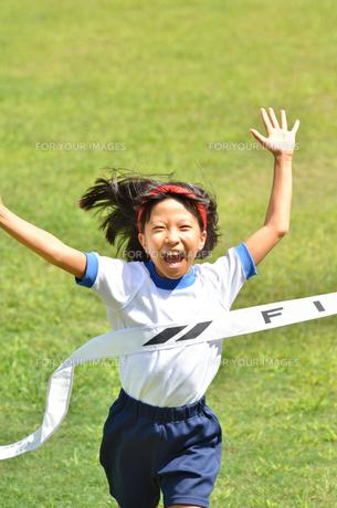 ゴールテープを切る小学生の女の子(芝生)の写真素材 [FYI00626803]