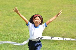 ゴールテープを切る小学生の女の子(芝生)の写真素材 [FYI00626804]
