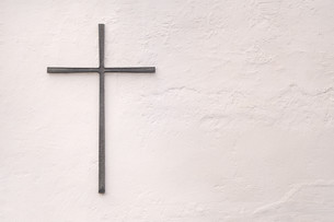 gray metal cross on a white wall with rough plasterの写真素材 [FYI00628377]