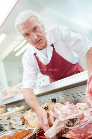 Butcher arranging his shop displayの写真素材 [FYI00630397]