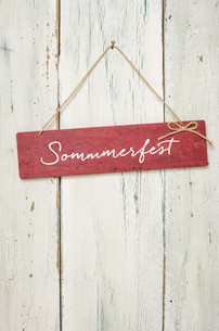 red wooden sign in front of a white wooden wall - summer festivalの素材 [FYI00630711]