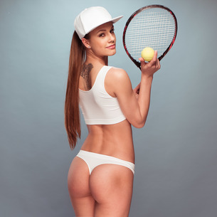 Sexy Female Tennis Player Holding Racket and Ballの写真素材 [FYI00631421]