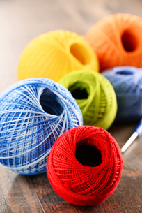 Colorful yarn for crocheting and hook on wooden tableの素材 [FYI00631612]