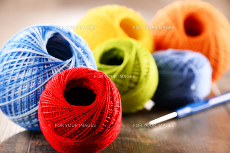 Colorful yarn for crocheting and hook on wooden tableの素材 [FYI00631615]