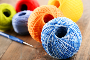 Colorful yarn for crocheting and hook on wooden tableの素材 [FYI00631617]