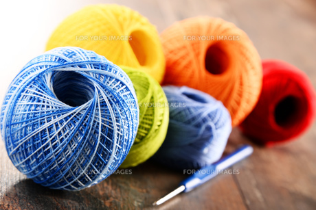 Colorful yarn for crocheting and hook on wooden tableの素材 [FYI00631619]