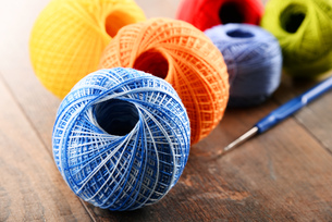 Colorful yarn for crocheting and hook on wooden tableの素材 [FYI00631621]