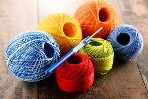 Colorful yarn for crocheting and hook on wooden tableの素材 [FYI00631625]