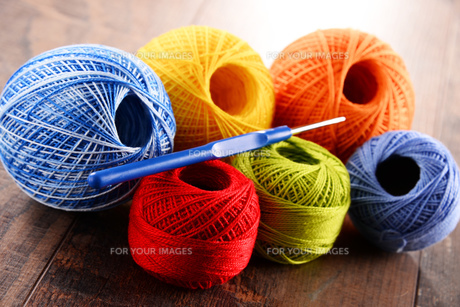Colorful yarn for crocheting and hook on wooden tableの素材 [FYI00631626]