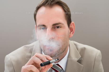 Businessman Smoking Electronic Cigaretteの写真素材 [FYI00634008]