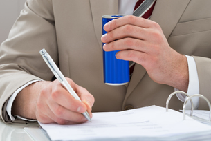 Businessman With Drink Can And Documentの写真素材 [FYI00634018]