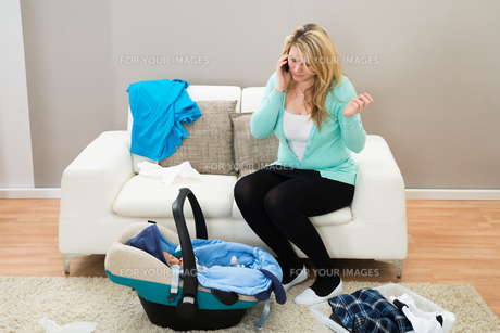 Woman Talking On Mobile In Living Roomの写真素材 [FYI00634023]