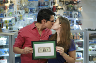 Happy Shop Owners kissing And Showing First Dollarの写真素材 [FYI00634109]