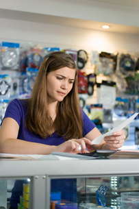 Worried Woman Checking Bills And Invoices With Calculatorの写真素材 [FYI00634114]