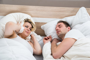 Woman Covering Ears While Man Snoringの写真素材 [FYI00634150]