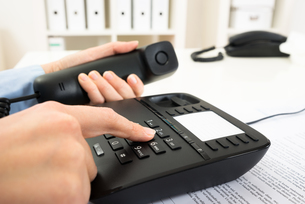 Businessperson Dialing Number On Telephone Keypadの写真素材 [FYI00634185]