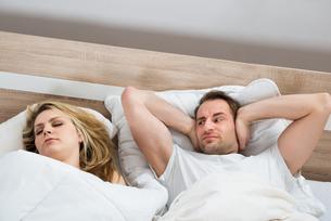 Man Covering Ears While Woman Sleepingの写真素材 [FYI00634302]