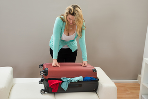 Woman Trying To Close The Suitcaseの素材 [FYI00634303]