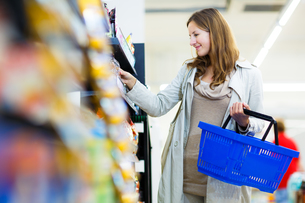 Beautiful young woman shopping in a grocery store/supermarket (color toned image)の写真素材 [FYI00634556]