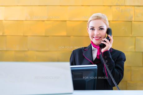 Hotel Rezeptionistin telefoniert mit Gastの素材 [FYI00634763]