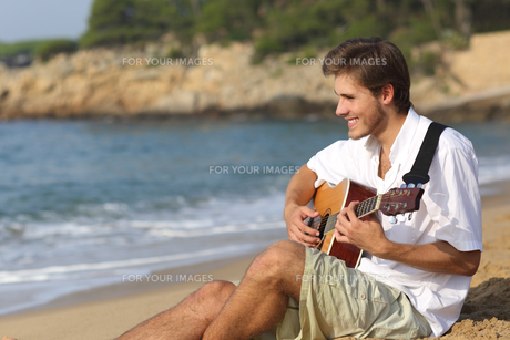 Handsome man playing classic guitar on the beachの写真素材 [FYI00634838]